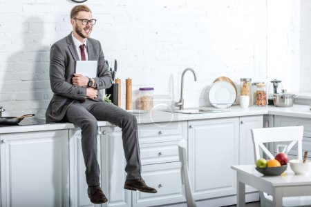 businessman sitting on countertop and holding laptop in kitchen at home