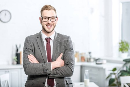 handsome businessman in glasses with arms crossed looking at camera