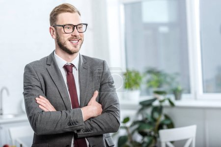 Photo for Handsome businessman in glasses with arms crossed looking away - Royalty Free Image