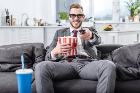 Photo pour Bel homme d'affaires sur le canapé dans des lunettes 3D avec télécommande regarder un film et manger du maïs soufflé - image libre de droit