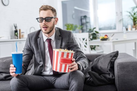 businessman on couch in 3d glasses with popcorn and soda water watching movie at home