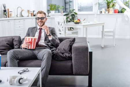 businessman on couch in 3d glasses watching movie and eating popcorn at home