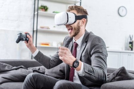 excited businessman wearing virtual reality headset and playing video game on couch at home