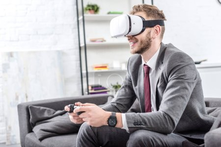smiling businessman wearing virtual reality headset and playing video game on couch at home