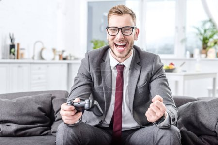 Photo for Excited businessman holding console and playing video game at home - Royalty Free Image