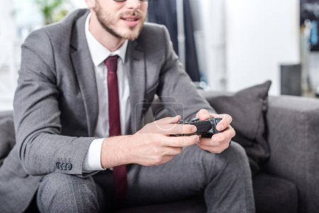 Photo for Cropped view of businessman holding console and playing video game at home - Royalty Free Image