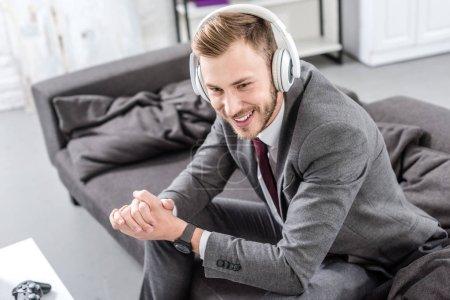 Photo pour Homme d'affaires souriant dans les écouteurs assis sur le canapé à la maison - image libre de droit