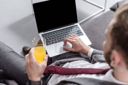 cropped view of businessman drinking orange juice and using laptop with blank screen