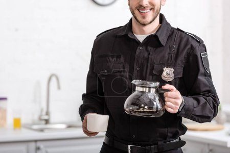 partial view of smiling policeman holding glass pot of filtered coffee at kitchen