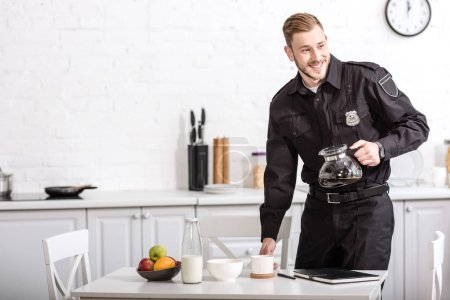 smiling handsome policeman holding glass pot of filtered coffee at breakfast time