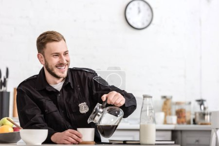 happy police officer pouring filtered coffee from glass pot at kitchen