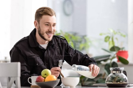 smiling policeman pouring milk into cereal bowl and having breakfast at kitchen