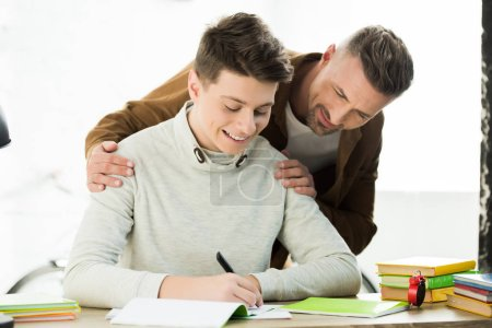 smiling father hugging teen son while he doing homework and writing something