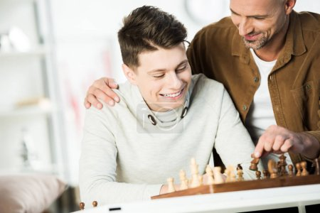 smiling father hugging happy teen son and playing chess at home
