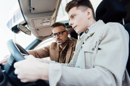 low angle view of stressed teen learning driving car, father looking away