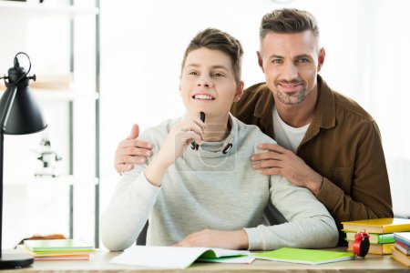 smiling father hugging pensive teen son while he doing homework