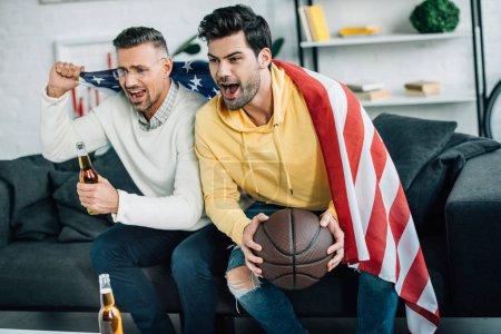 Photo pour Excité fils et père mature enveloppé dans drapeau des États-Unis regarder match de basket-ball et crier le week-end à la maison - image libre de droit