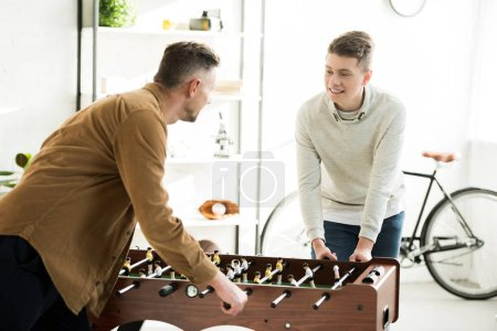 Photo for Father and teen son playing table football together at home - Royalty Free Image