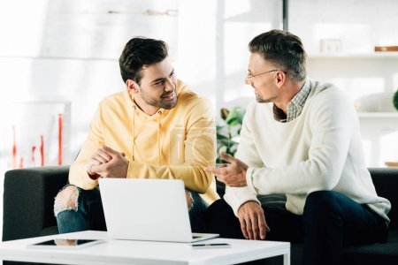 son and mature father sitting neat table with laptop and talking at home