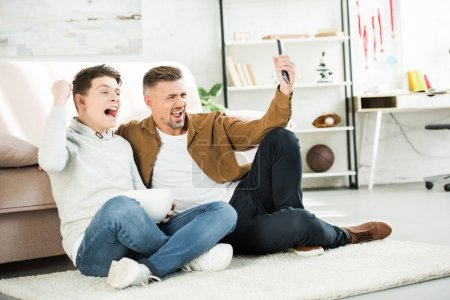 excited father and teen son watching match on tv and holding bowl of popcorn at home