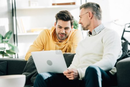 handsome son looking at mature father using laptop on sofa at home