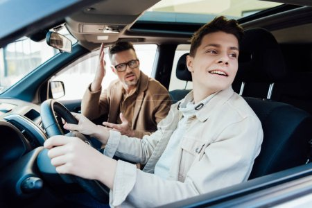 irritated father teaching smiling teen son driving car