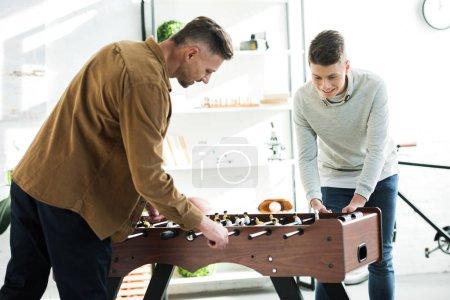 Ojciec i syn gra w domu piłkarzyki.