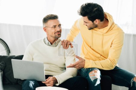 Photo for Son and mature father with laptop looking at each other on sofa at home - Royalty Free Image