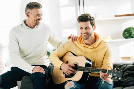 cheerful son playing acoustic guitar for mature father on weekend at home