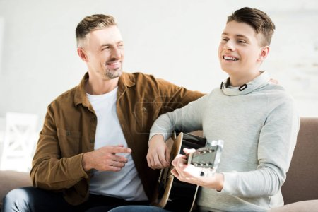 smiling teen son playing acoustic guitar for father at home