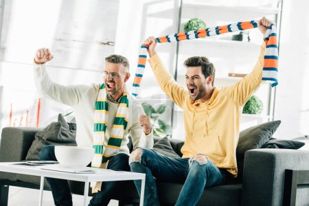 excited son and mature father with scarfs watching sport and screaming at home