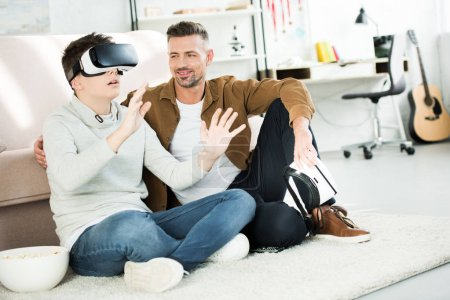 Photo for Cheerful father looking at teen son watching something with virtual reality headset at home - Royalty Free Image