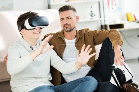 Foto de Padre mira hijo adolescente viendo algo con casco de realidad virtual en casa - Imagen libre de derechos