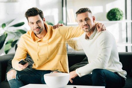 Photo pour Fils et le père mature étreindre et regardent la télévision ensemble week-end à la maison - image libre de droit