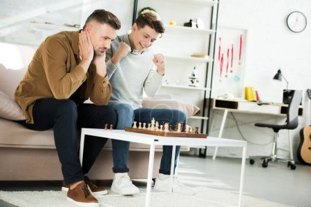 smiling teen son winning chess while playing with father at home