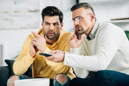 serious son and mature father watching tv together on weekend at home