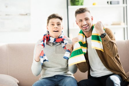 excited father and teen son in scarfs watching sport match and gesturing at home