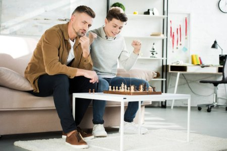 happy teen son winning chess while playing with father at home