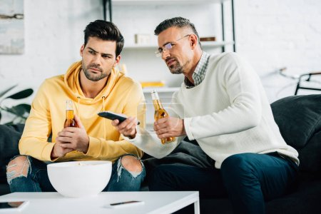son and mature father watching tv with beer on weekend at home