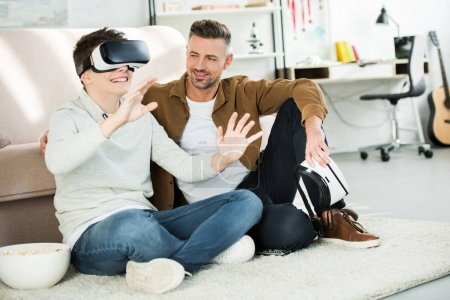 father looking at teen son watching something with virtual reality headset at home