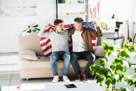 Photo pour Heureux père et fils adolescent enveloppé dans le drapeau des États-Unis assis sur le canapé et crier durant les match de sport - image libre de droit