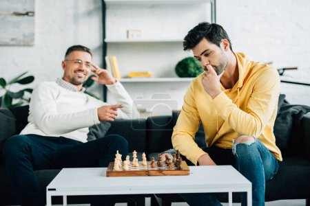 pensive son and smiling mature father playing chess together on weekend at home