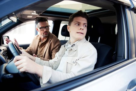 Photo for Handsome father looking at teen son learning driving car - Royalty Free Image