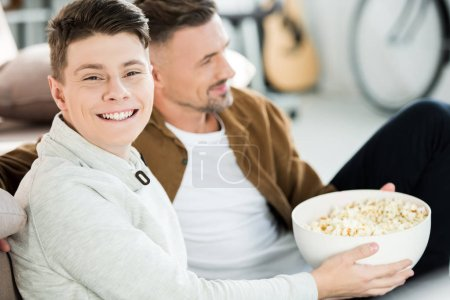 portrait of father and happy teen son watching tv and holding bowl of popcorn at home