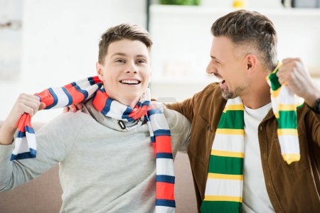 excited happy father and teen son in scarfs watching sport match at home