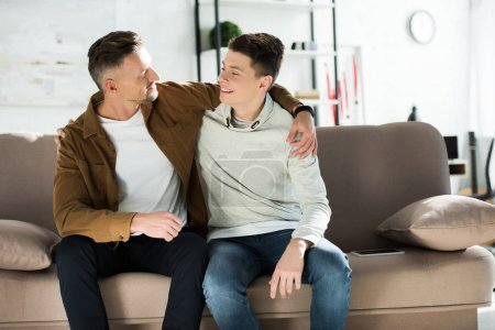 Photo for Happy father and teen son hugging on sofa at home - Royalty Free Image