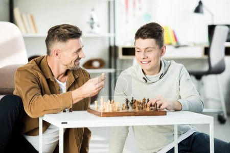 Photo for Smiling father showing chess figure to teen son while playing chess at home - Royalty Free Image