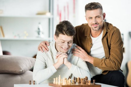 cheerful father hugging teen son while playing chess at home