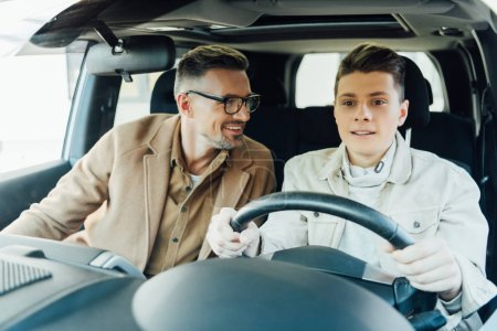 smiling handsome father teaching teen son driving car and looking at him