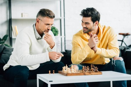 handsome son and mature father playing chess on weekend at home